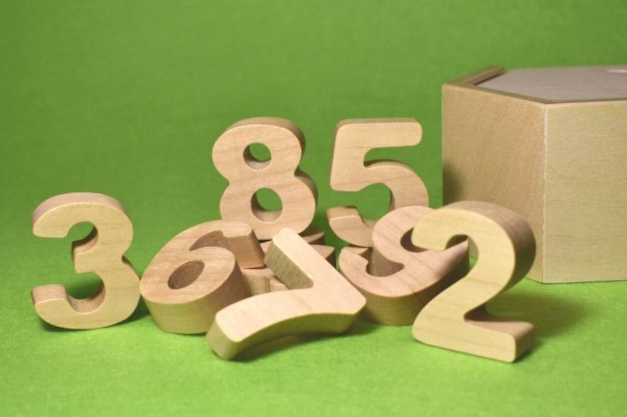 Объемные цифры из дерева на зеленом фоне