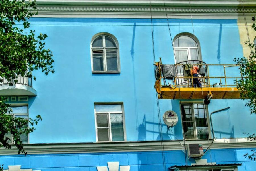 Рабочие в строительной люльке на фасаде здания